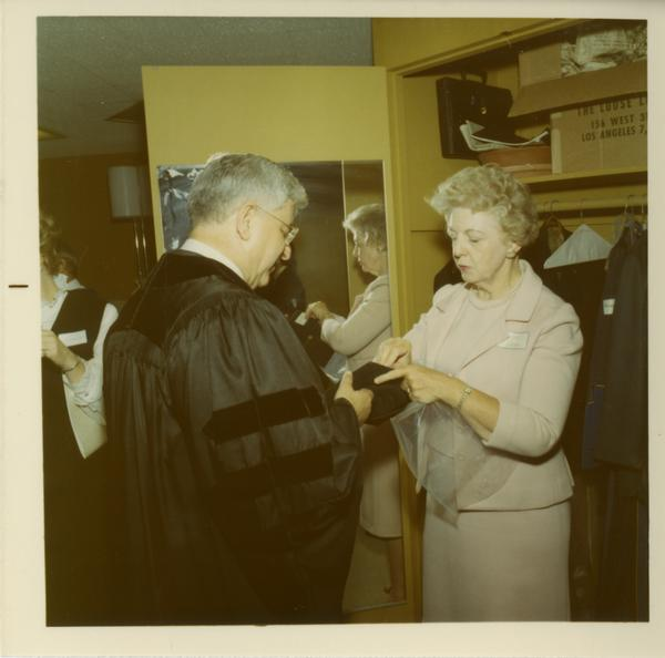 Woman assisting man with his hood at Commencement, June 17, 1970
