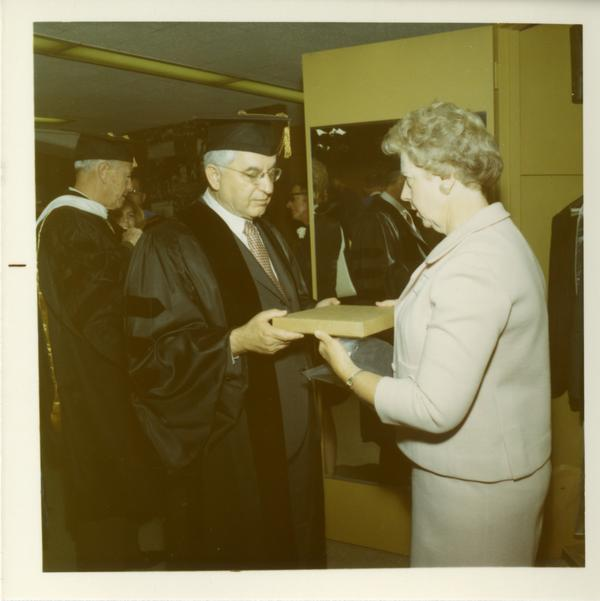 Commencement participant is handed a package by a woman, June 17, 1970