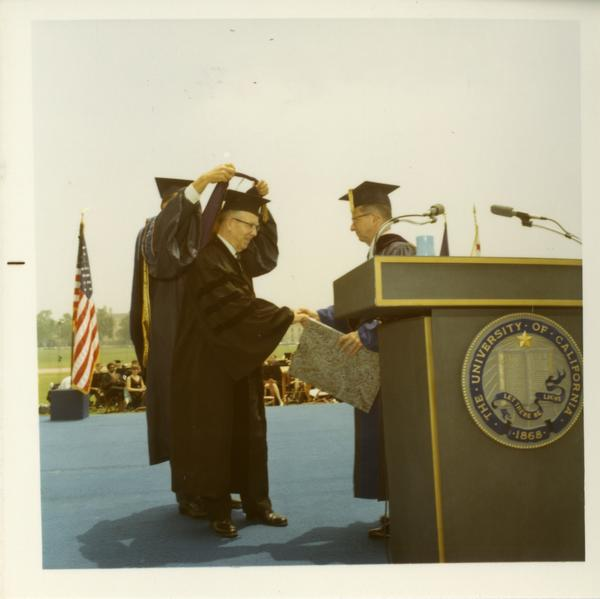 Honorary degree recipient shaking hands with unidentified man on stage at Commencement, June 17, 1970