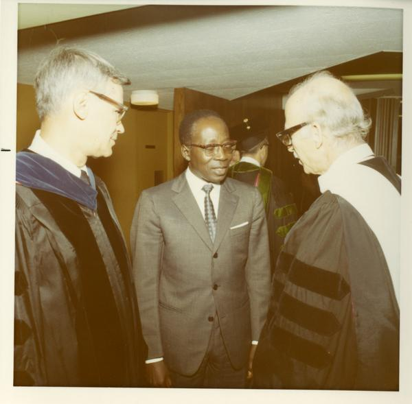 Commencement participants talking with an unknown man at Commencement, 1971
