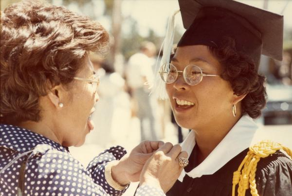 Woman having her robe adjusted by a woman, possibly her mother, at commencement, 1974