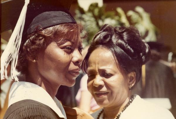 Graduate looks into the distance next to a woman, possibly her mother, at commencement, 1974
