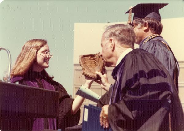 Darlene Walsh presents a baseball glove to Chancellor Young and Marshal Waldo Phelps at commencement, June 1976