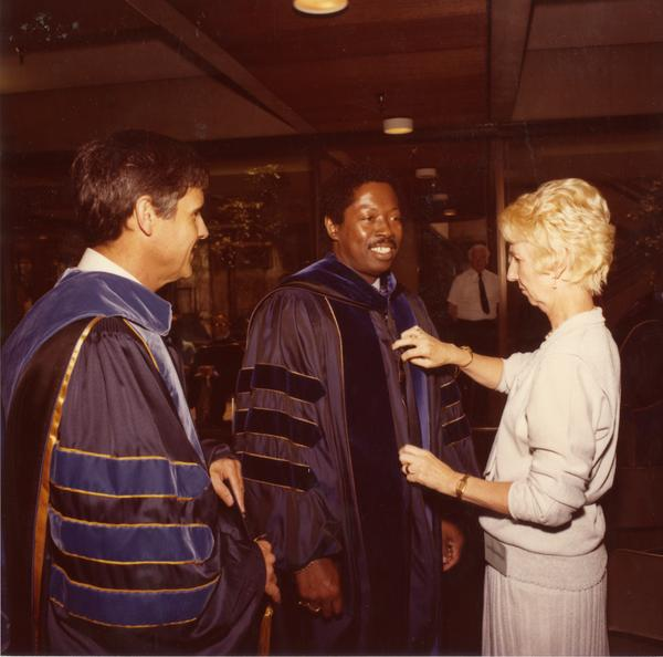 Woman assists two platform party members with their robes for commencement, June 1979
