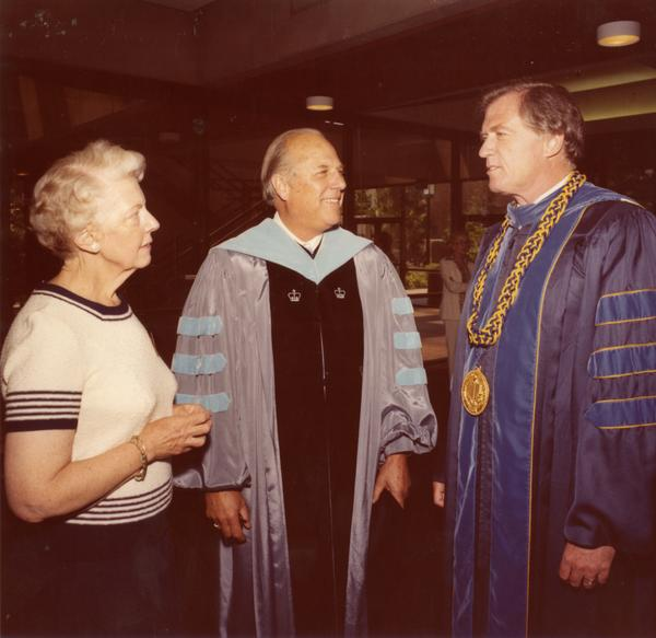 Chancellor Charles E. Young with Patty Carew and another man of the platform party talking at commencement, June 1979