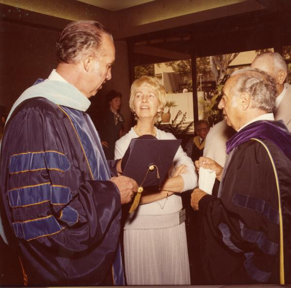 Elwin Svenson and Charles Speroni talking with a woman at commencement, June 1979