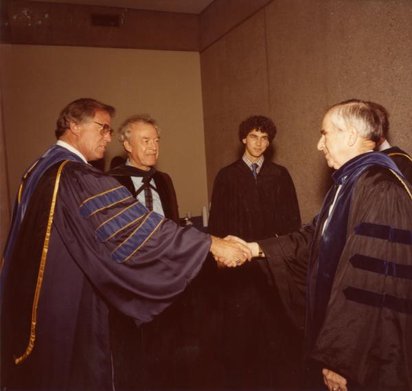 Two members of the party platform shake hands at commencement, June 1979