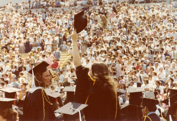 Graduate waves to those in the crowd at commencement, June 1979