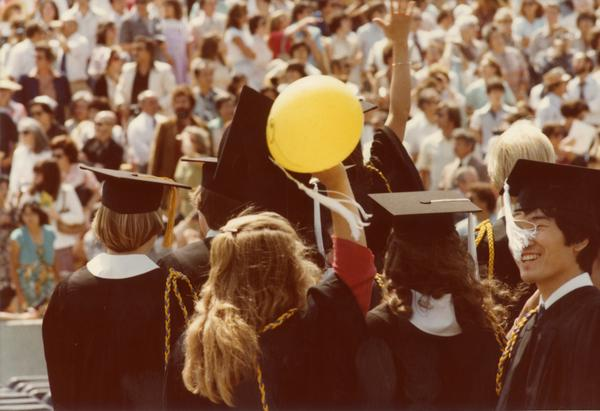 Graduates wave to those in the audience at commencement, June 1979
