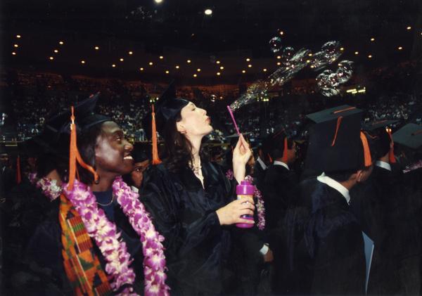 Graduate blows bubbles at commencement, ca. 1990's