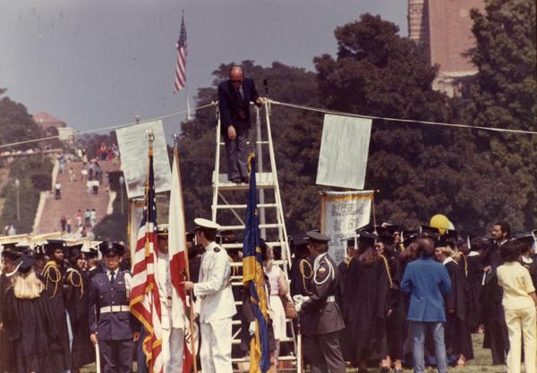 Commencement worker climbs down a ladder while graduates stand around