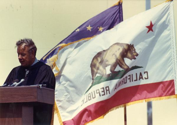Member of the party platform addresses the audience with the California flag flying behind him at commencement