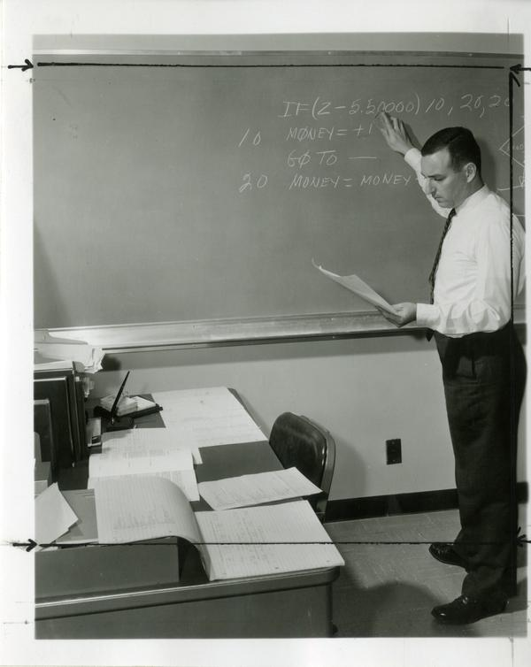 Man reviews notes on the chalkboard at the Western Data Processing Center