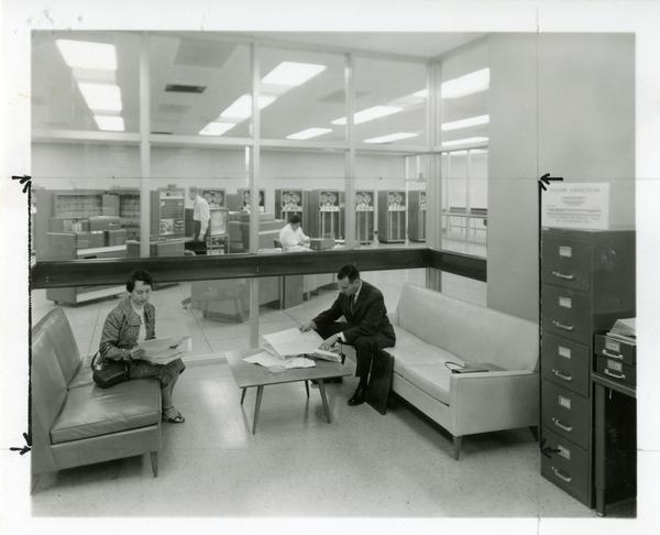 Two individuals sit on couches, reviewing notes at the Western Data Processing Center