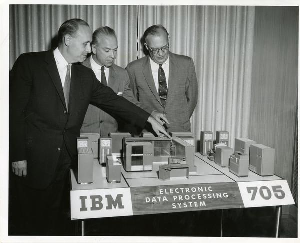 Dr. Cuthbert C. Hurd, Dean Neil Jacoby, and Chancellor Raymond B. Allen looking at a model of the IBM 705 computer for the Western Data Processing Center