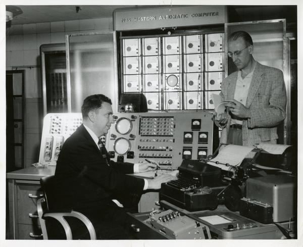 Two workers at equipment desks at the Western Data Processing Center