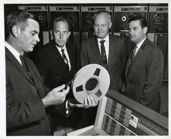 One worker holds a reel of taype while three others, including chancellor Franklin D. Murphy, look on at the Western Data Processing Center, ca. 1960's