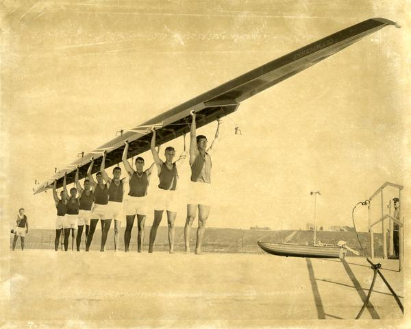 Members of the Varsity Crew team holding up their shell, 1968