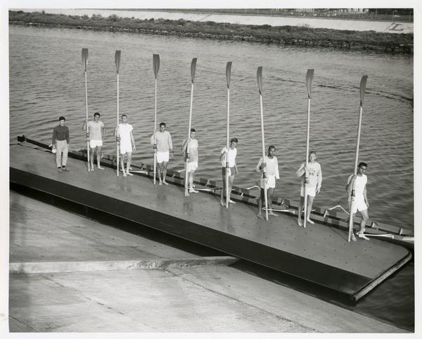 Members of the Varsity Crew team standing on the dock, holding their rowing equipment, 1968