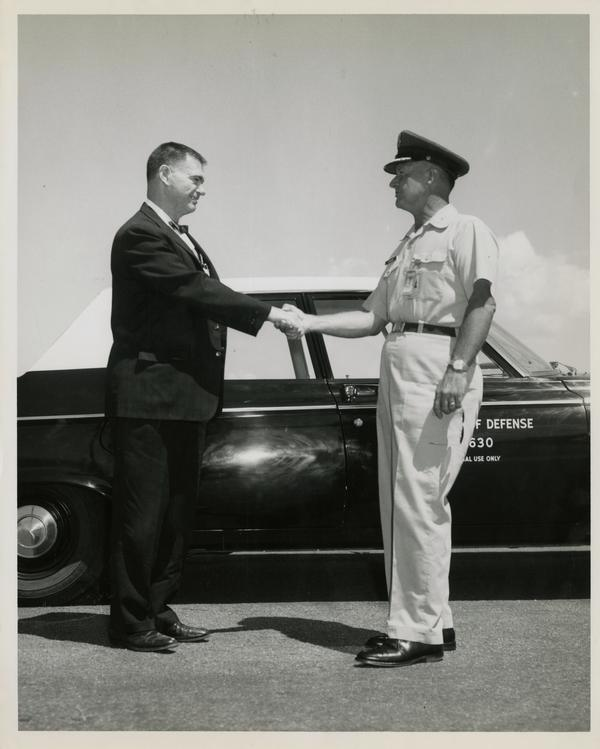 Two attendees, William G. McMillan standing left, of the Defense Science Seminar shaking hands, ca. 1965