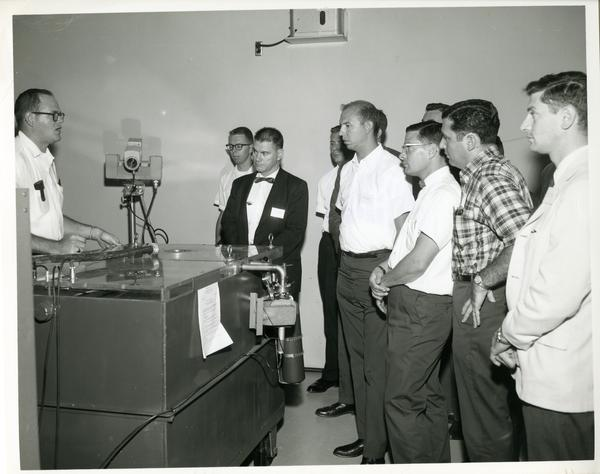 Members of the Defense Science Seminar looking at some equipment, ca. 1965