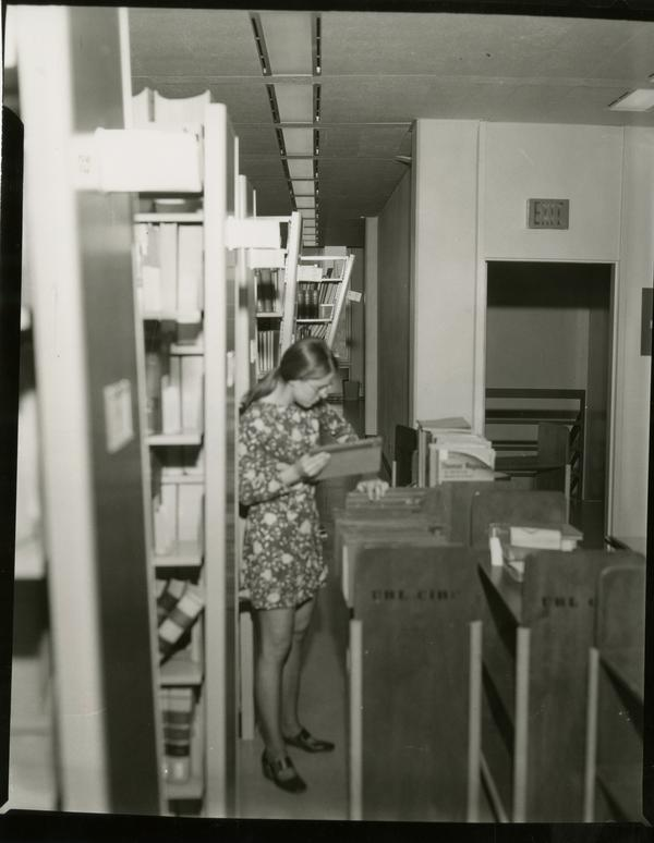 Library assistant cleans up after damage from the earthquake, 1971