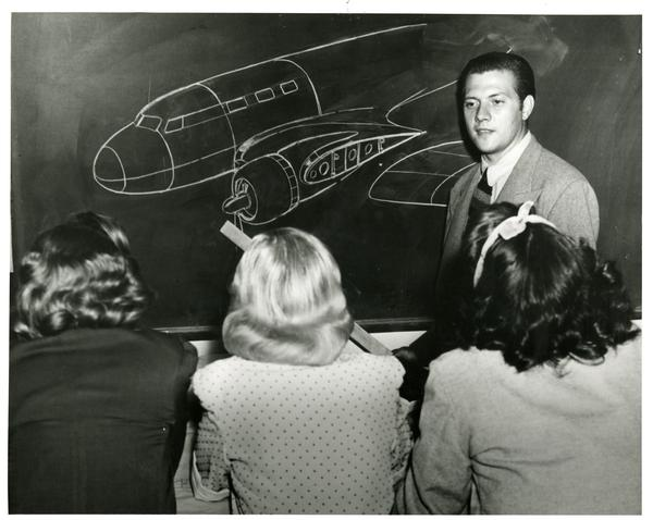 Teacher gesturing at plane drawn on blackboard