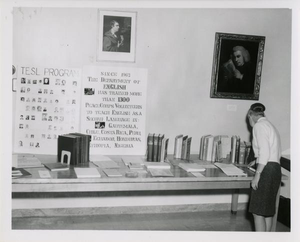Woman looks at books and papers set out for display in the English Reading Room for an UCLA Open House