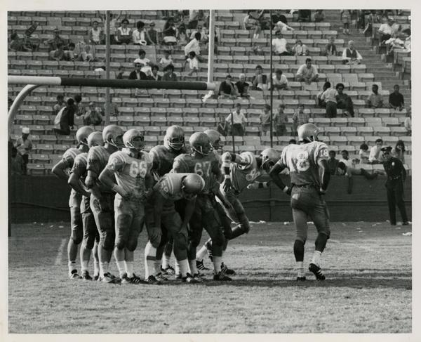 Football team gathered on the field during a game, ca. 1960s