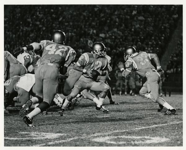 UCLA Quarterback Scott Henderson (12) prepares to hand off to Fullback Randy Tyler (33) with Flankerback Mike Cochran (42) coming around on the fake reverse against Oregon State.