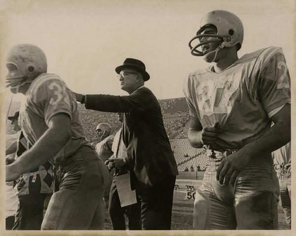 UCLA football coach Tommy Prothro motioning to another athlete during a game