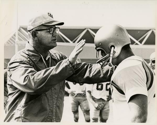 UCLA football coach Tommy Prothro working with an athlete on defense