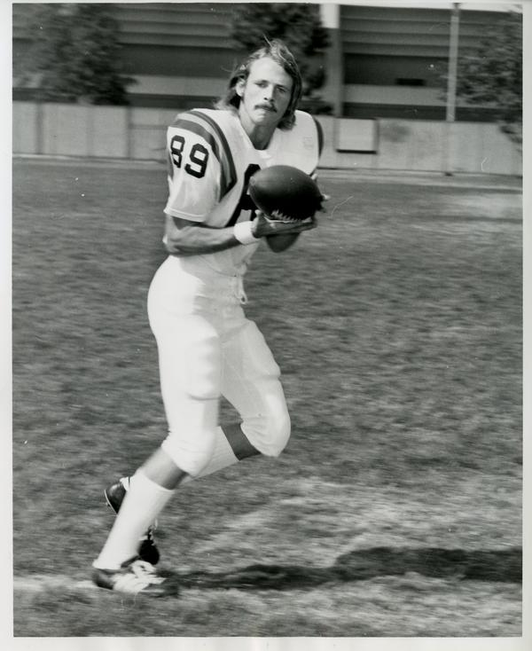 UCLA football player Norm Andersen catching a pass in practice