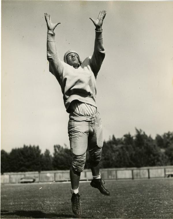 UCLA football player James Millette reaching for a football, 1947
