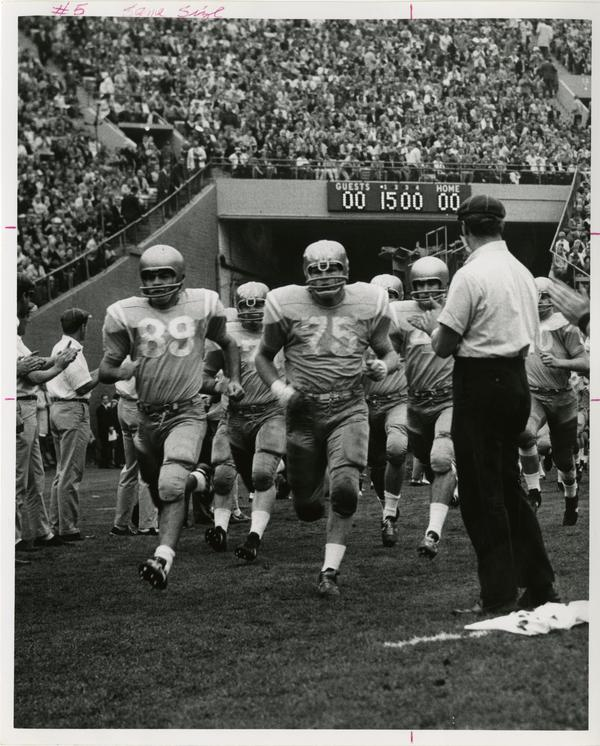 UCLA football player John Richardson running with the rest of the team onto the field for a game