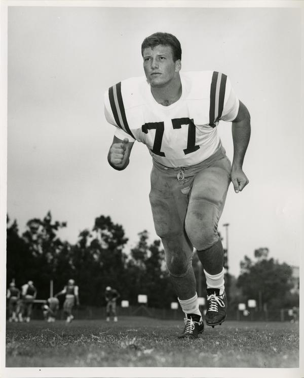UCLA right tackle Larry Sleagle running on the field, 1966