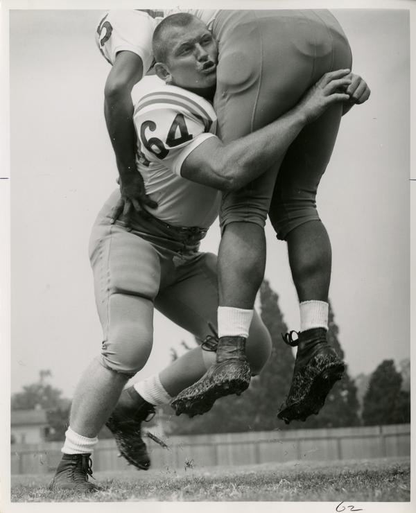 UCLA left guard and right linebacker John Walker tackling a player in practice, 1963