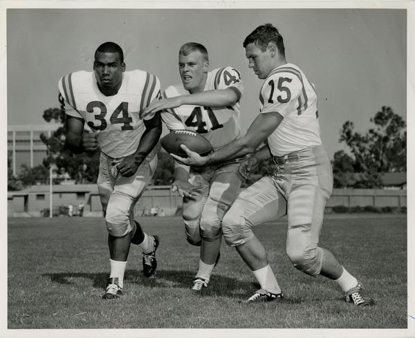 UCLA football player Larry Zeno practicing a handoff