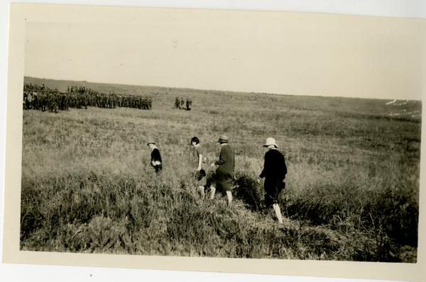 Four attendees of the campus dedication walking through a field, 1926