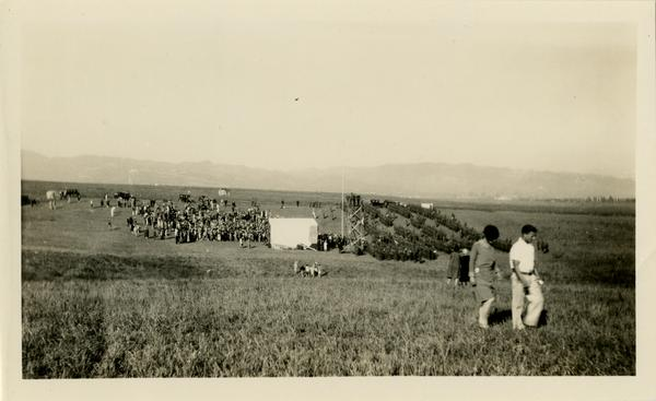 Two attendees walk away from the stage area of the dedication of the new campus, October 1926