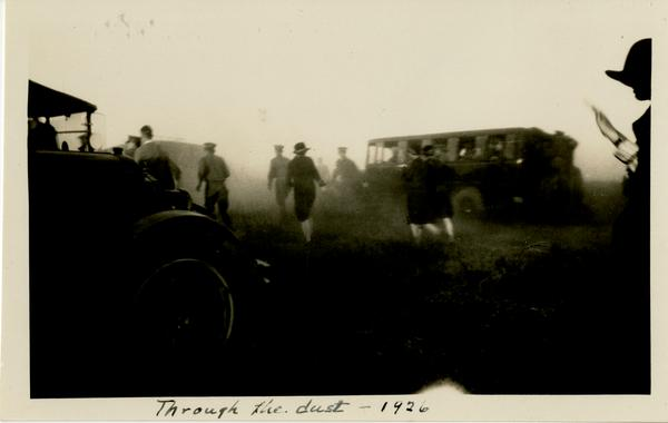 Dedication attendees walking through the dust caused by cars arriving to the dedication area, October 1926
