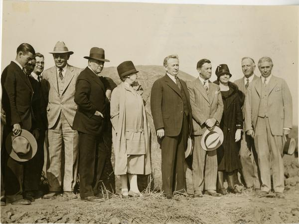 Dr. Edwin James, James R Martin, Regent Sarton, Governor Young, Regent Durham, Mrs. Roeber, Dr Rieber, Judge Russ Avery, Thomas J Armingham and Dr. Walderman Westagard pose together in front of Founder's Rock