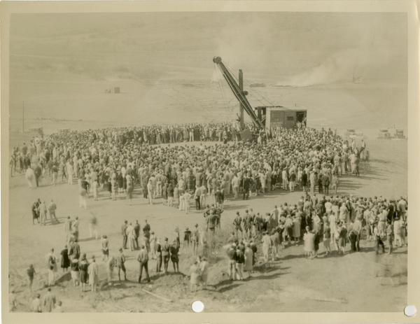 Crowd gathered for new campus dedication looks on as crane places stone, October 1926
