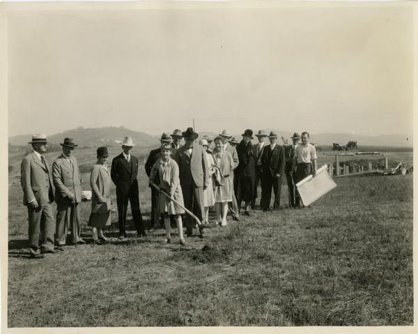 Child with shovel breaks ground for first buiding at new campus groundbreaking ceremony, October 1926