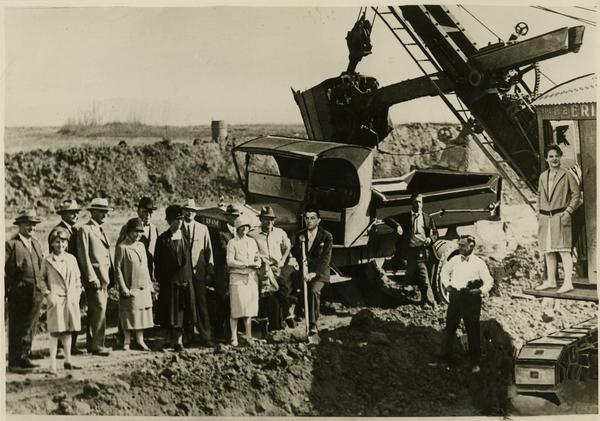 Man posing with shovel has fake face superimposed over his at new campus groundbreaking ceremony, October 1926