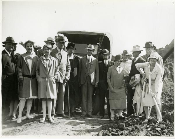 Woman with shovel poses with group at new campus groundbreaking ceremony, October 1926