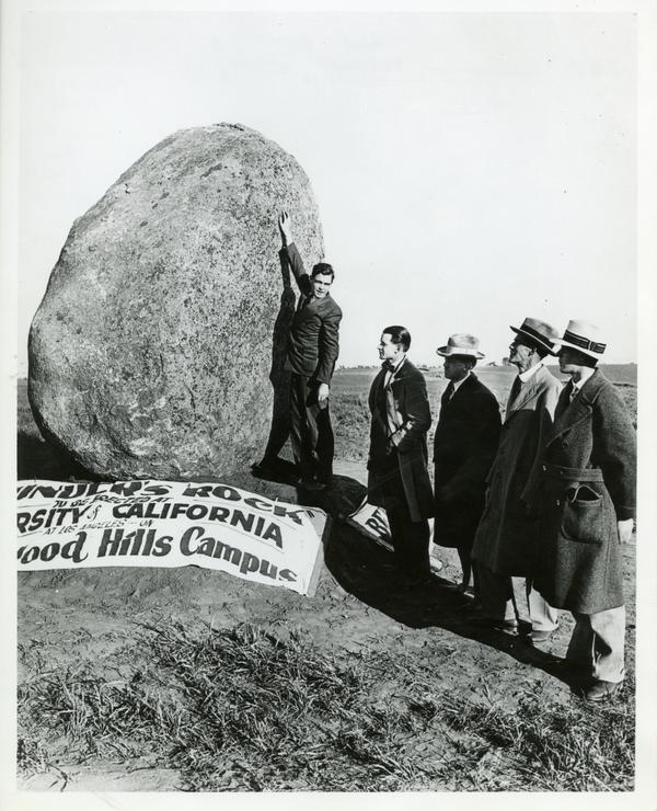 Bob Huff, a student, Regent Edward A. Dickson, and Earle Hedrick (later UCLA Provost at this time a math professor at UCLA) standing next to the Founder's Rock, which is in a vertical position