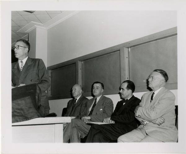 Looking at men including Lawrence Clark Powell, sitting behind speaker at podium during Friends of the UCLA Library event
