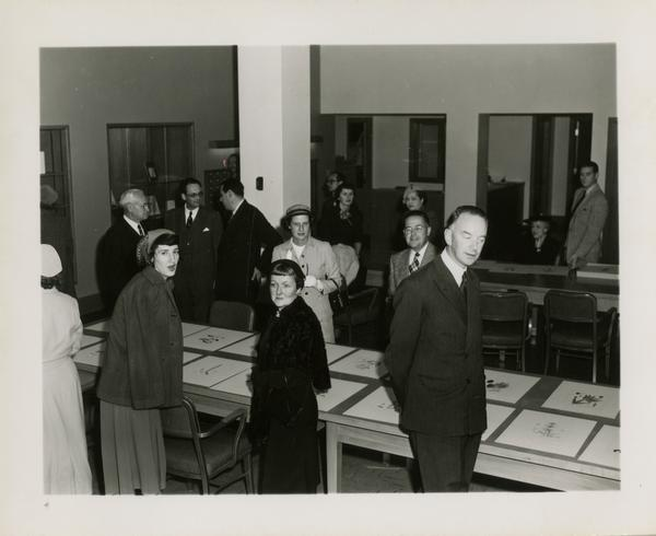 Members of Friends of the UCLA Library looking at large prints
