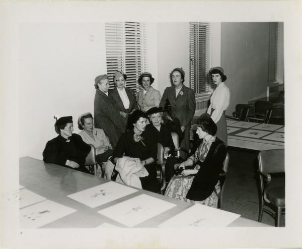 Members of the Friends of the UCLA Library group seated and standing around table